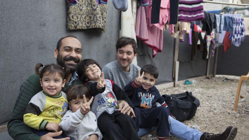 Father and kids laughing in a refugee camp in Akkar