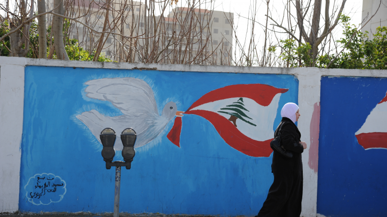 Woman walking in Saida in front of a painted wall
