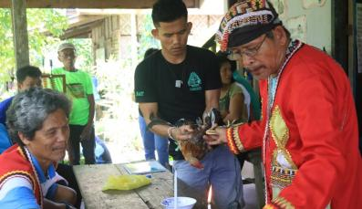 Indigenous youth assist their traditional leader in a ritual
