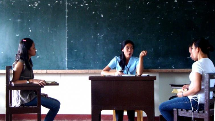 Three students discussing in a classroom